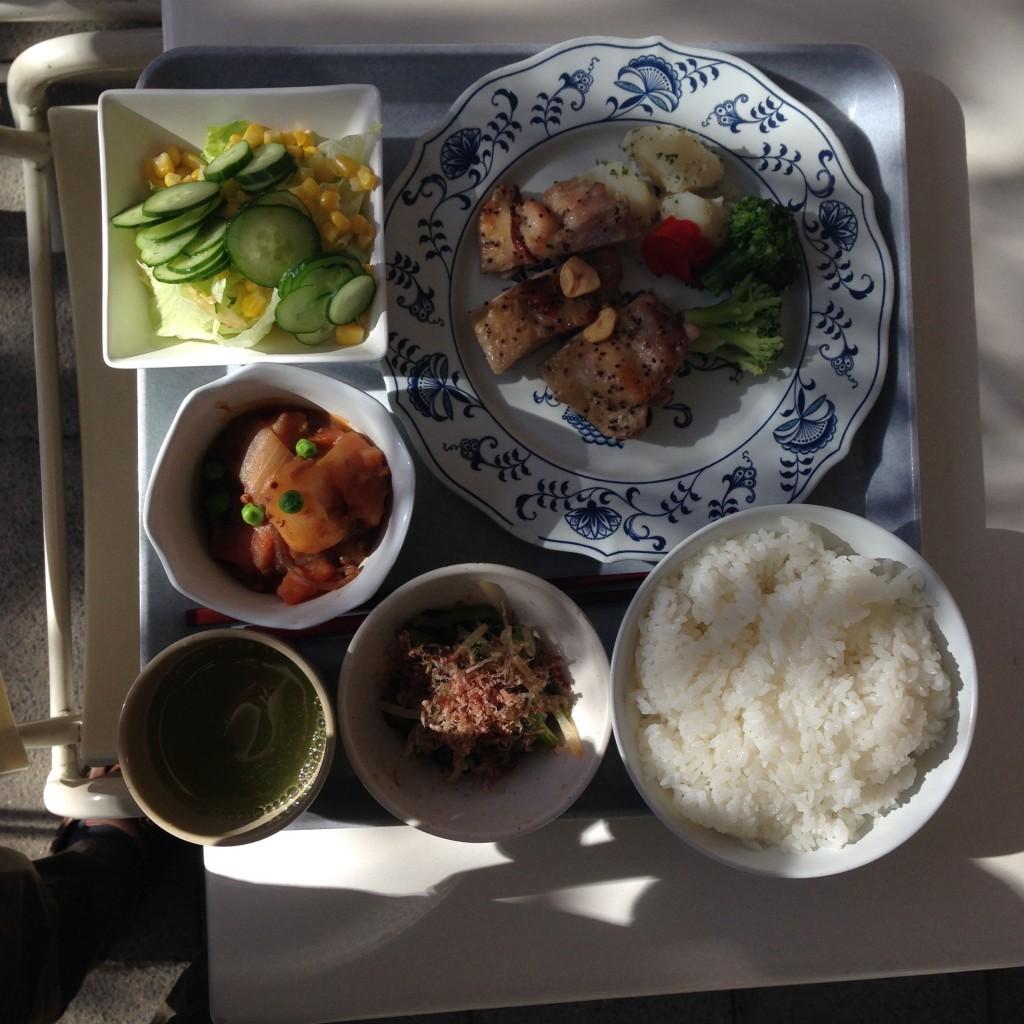klassische Mahlzeit mit Reis, Grüntee, Huhn in schwarzem Sesam, Salat, Spinatsalat mit hauchdünnen  Scheiben von getrocknetem Thunfisch und einem Salat mit Kartoffeln